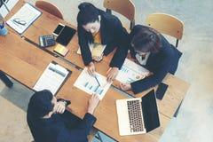 Деловые партнеры взгляда сверху тренируя и обсуждая контракт и диаграмму финансового развития отчета стоковые изображения