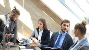 Деловые партнеры обсуждая документы и идеи на встрече стоковое изображение rf