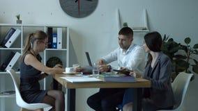 деловые партнеры обсуждая документы на встрече акции видеоматериалы