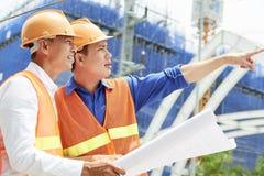 Деловые партнеры обсуждая строительный проект стоковая фотография rf