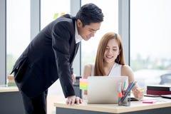 деловые партнеры объединяются в команду работать совместно на столе с компьтер-книжкой и документом Бизнесмен используя ноутбук и стоковая фотография