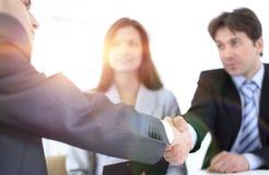 Деловые партнеры рукопожатия в рабочем месте стоковое изображение