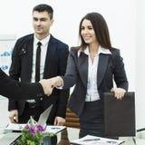 деловые партнеры рукопожатия на встрече около настольного компьютера в современном офисе Стоковые Изображения