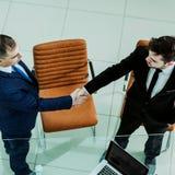 Деловые партнеры рукопожатия около настольного компьютера, в просторном офисе Стоковые Изображения