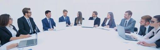 Деловые партнеры собрали вокруг таблицы и обсуждают financi Стоковое Фото