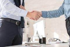 Деловые партнеры тряся руки над таблицей стоковые изображения