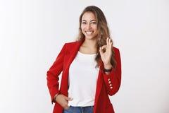 Дело девушки полностью уверенное уверенное уже ее руки, показывая руку в порядке жеста ок усмехаясь удачливую само-уверенную держ стоковые изображения
