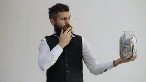 Бородатый человек держа опарник вполне денег изолированных на белой предпосылке Получать богатый Дело, деньги, люди и акции видеоматериалы