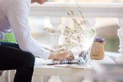 Дело дело компьтер-книжки онлайн делая долларовые банкноты денег Стоковая Фотография