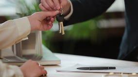 Дело, недвижимость, дело и концепция людей - укомплектуйте личным составом давать ключи дома к женщине на офисе сток-видео