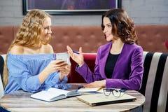 Дело обсуждения 2 молодой женщины в вскользь одежде говоря и показывать, сидя на таблице Стоковая Фотография