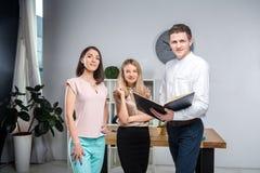 Дело, сыгранность и партнерства темы Группа в составе молодые люди, 3 люд, стойка в офисе около таблицы внутри стоковая фотография rf