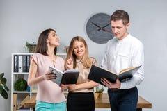 Дело, сыгранность и партнерства темы Группа в составе молодые люди, 3 люд, стойка в офисе около таблицы внутри стоковые изображения