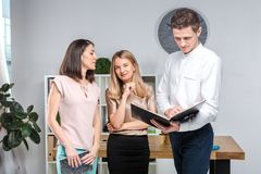Дело, сыгранность и партнерства темы Группа в составе молодые люди, 3 люд, стойка в офисе около таблицы внутри стоковые изображения rf