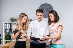 Дело, сыгранность и партнерства темы Группа в составе молодые люди, 3 люд, стойка в офисе около таблицы внутри стоковое фото rf
