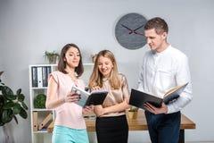 Дело, сыгранность и партнерства темы Группа в составе молодые люди, 3 люд, стойка в офисе около таблицы внутри стоковое изображение