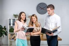 Дело, сыгранность и партнерства темы Группа в составе молодые люди, 3 люд, стойка в офисе около таблицы внутри стоковая фотография