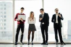 Дело, сыгранность, люди и концепция технологии - команда дела при компьютеры и smartphones ПК таблетки встречая в офисе снова Стоковое Фото