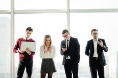 Дело, сыгранность, люди и концепция технологии - команда дела при компьютеры и smartphones ПК таблетки встречая в офисе снова Стоковые Изображения