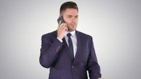 Дело, технология и концепция людей - усмехаясь бизнесмен со смартфоном говоря на предпосылке градиента сток-видео