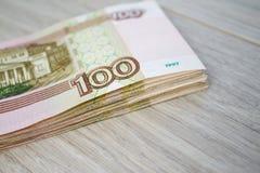 Дело, финансы, сбережения, концепция банка - близкая поднимающая вверх пачка банкнот денег русских 100 рублей Стоковое Изображение