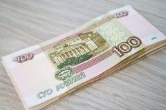 Дело, финансы, сбережения, концепция банка - близкая поднимающая вверх пачка банкнот денег русских 100 рублей Стоковая Фотография RF