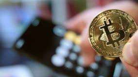 Дело cryptocurrency Bitcoin Вычисление выгоды Человек держа монетку bitcoin сток-видео
