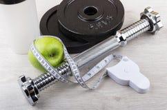 Демонтированная гантель, зеленое яблоко и лента измерений Стоковое Фото