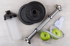Демонтированная гантель, пластичный шейкер, зеленые яблоки и измерения Стоковое фото RF