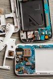 Демонтированные части сотового телефона на деревянном столе стоковые изображения rf