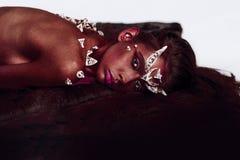 Демон с гореть красную кожу Женский изверг с терниями на плечах и рожками на голове лежа на поле изолированном на белизне стоковое изображение rf