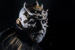 Демон с золотым воротником на черной предпосылке Человек с терниями или бородавочками, стороной предусматриванной с яркими блеска Стоковое Изображение