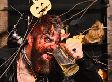 Демон с рожками и злой стороной улыбки выпивает эль Концепция партии хеллоуина Человек нося страшный состав держит пиво стоковые изображения rf