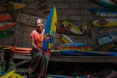 Демон Ibu мастер от Ubud Каждый день она сделала мини ремесла шлюпки прибоя которые были нарисованы и были покрашены используя яр стоковые фото