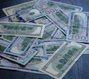 100 деноминаций доллара положены вне на предпосылку дерева Стоковая Фотография RF