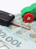 Деньги, автомобиль игрушки зеленого цвета и корабль ключа Белая предпосылка Стоковые Изображения