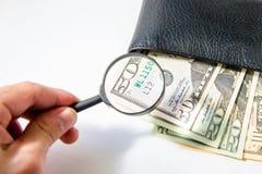 Деньги, 100 американских долларов под лупой в черном кожаном портмоне на белой предпосылке Стоковая Фотография RF