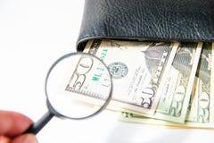 Деньги, 100 американских долларов под лупой в черном кожаном портмоне на белой предпосылке Стоковые Фото