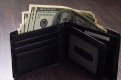 Деньги в кожаном бумажнике на таблице Стоковое Изображение