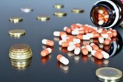 Деньги евро с medicaments Отражать eurocoins и пилюльки стоковое изображение