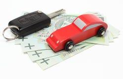 Деньги, деревянный красный автомобиль игрушки и корабль ключа Белая предпосылка Стоковое Фото