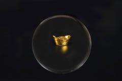 Деньги золотого ингота через стеклянный хрустальный шар Стоковые Фотографии RF