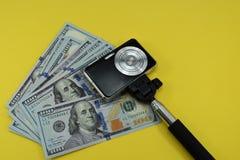 Деньги и камера фото на желтой предпосылке стоковая фотография