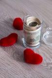 Деньги и красные сердца Доллары в открытом опарнике на серой деревянной предпосылке скопируйте космос Любовь вектор Валентайн илл Стоковая Фотография