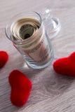 Деньги и красные сердца Доллары в открытом опарнике на серой деревянной предпосылке скопируйте космос Любовь вектор Валентайн илл Стоковые Фото