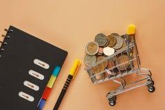 Деньги и монетки в мини магазинной тележкае или вагонетке с спиралью не стоковые фотографии rf