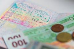 Деньги и пасспорт с штемпелями визы стоковое изображение