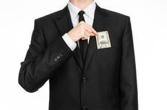 Деньги и тема дела: человек в черном костюме держа счет 100 долларов и отличает жестом рукой на изолированном белом bac Стоковые Изображения