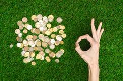 Деньги и тема финансов: Монетки денег и человеческий показ руки показывать на предпосылке взгляд сверху зеленой травы стоковые изображения rf