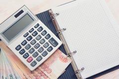 Деньги, калькулятор и тетрадь Стоковое Фото